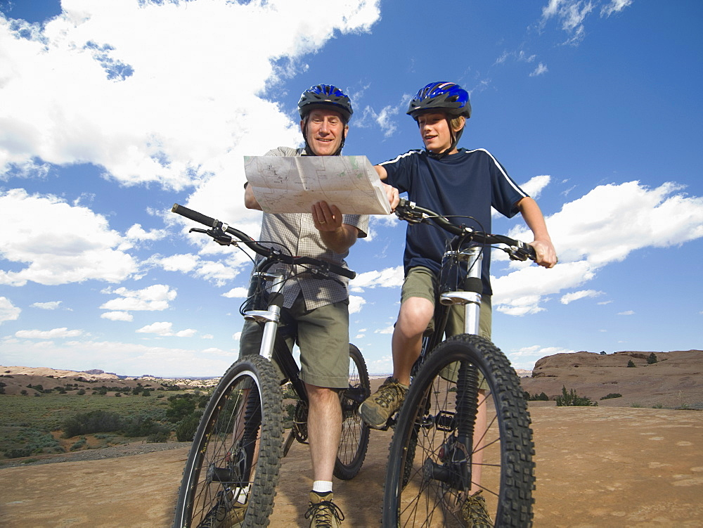 Father and son on mountain bikes with map
