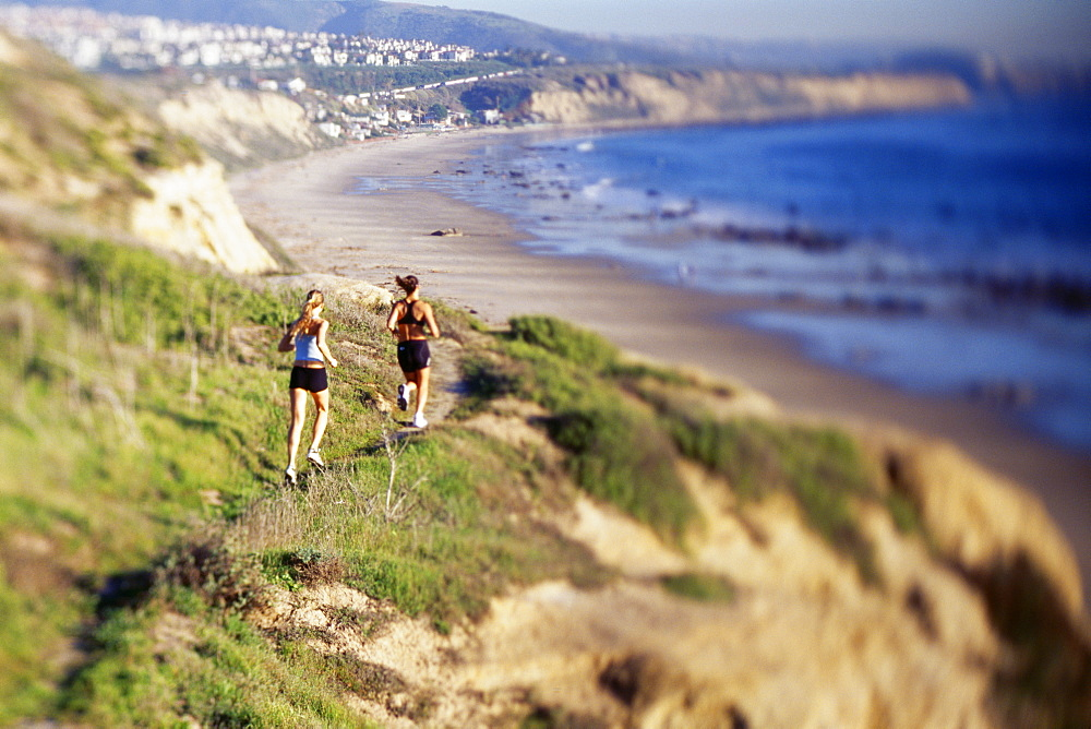Women jogging on cliff along water