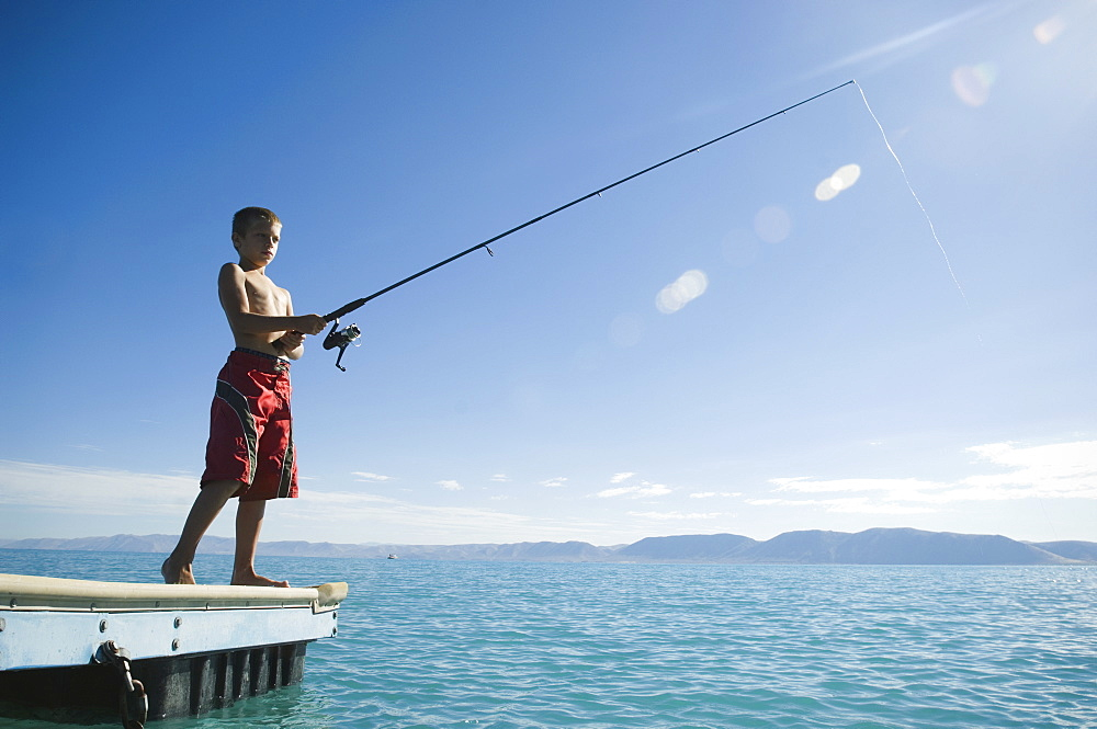 Boy fishing off dock in lake, Utah, United States