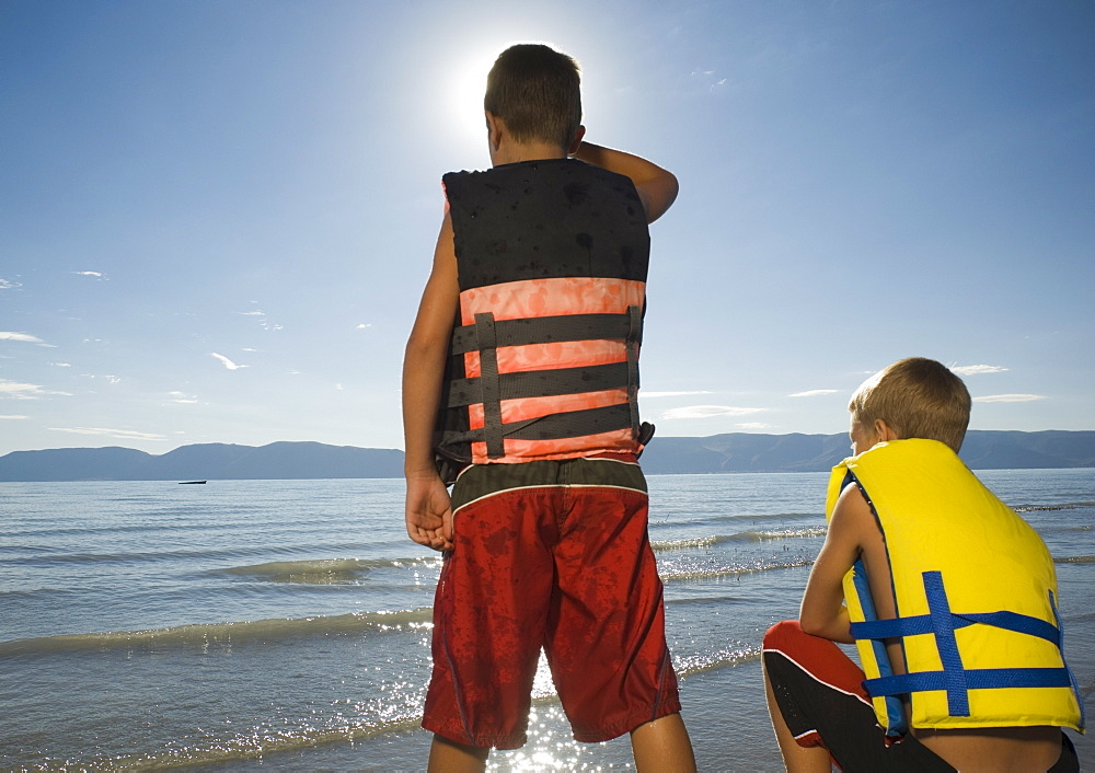 Boys in life jackets looking out over lake, Utah, United States