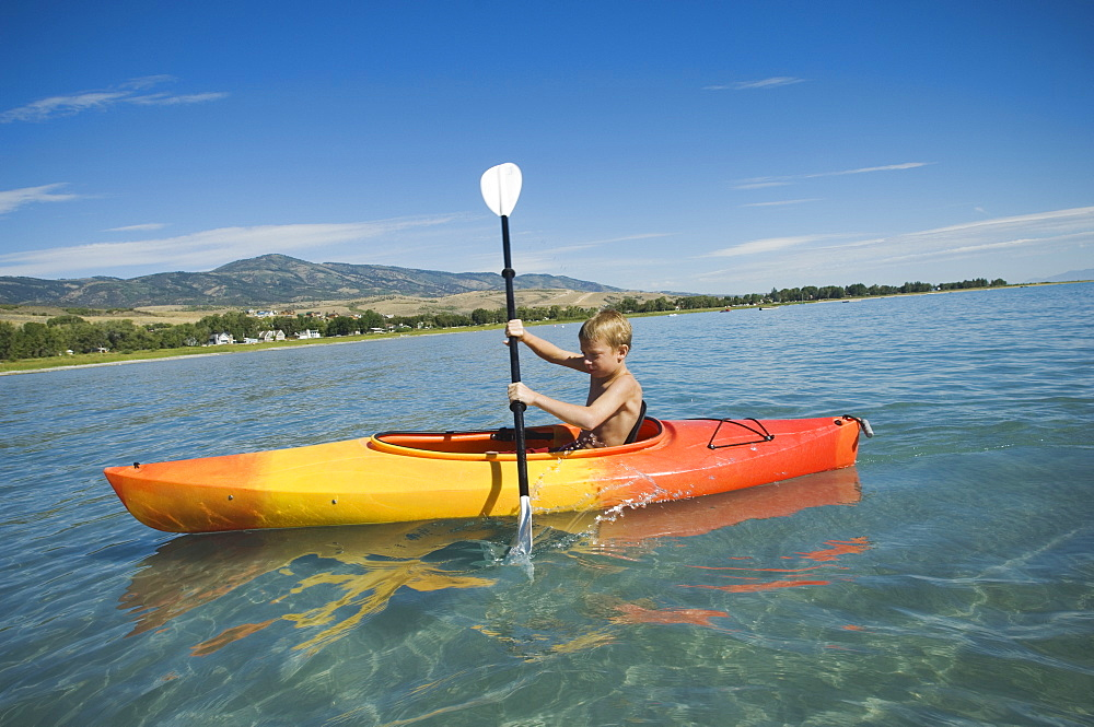 Boy paddling in canoe on lake, Utah, United States