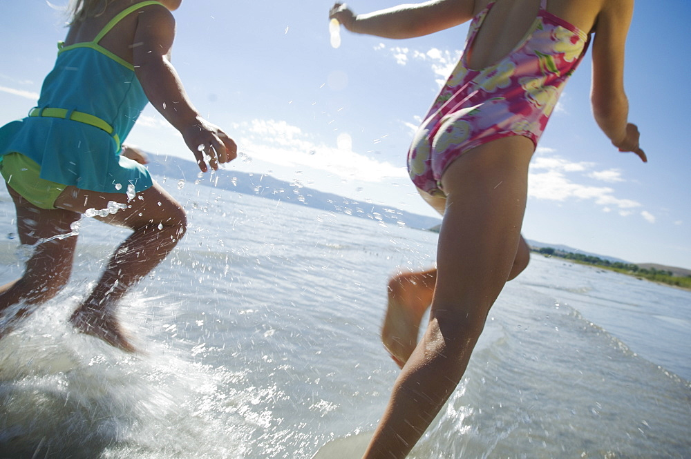 Sisters running in water, Utah, United States