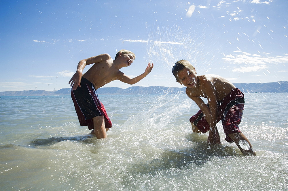 Brothers splashing in lake, Utah, United States