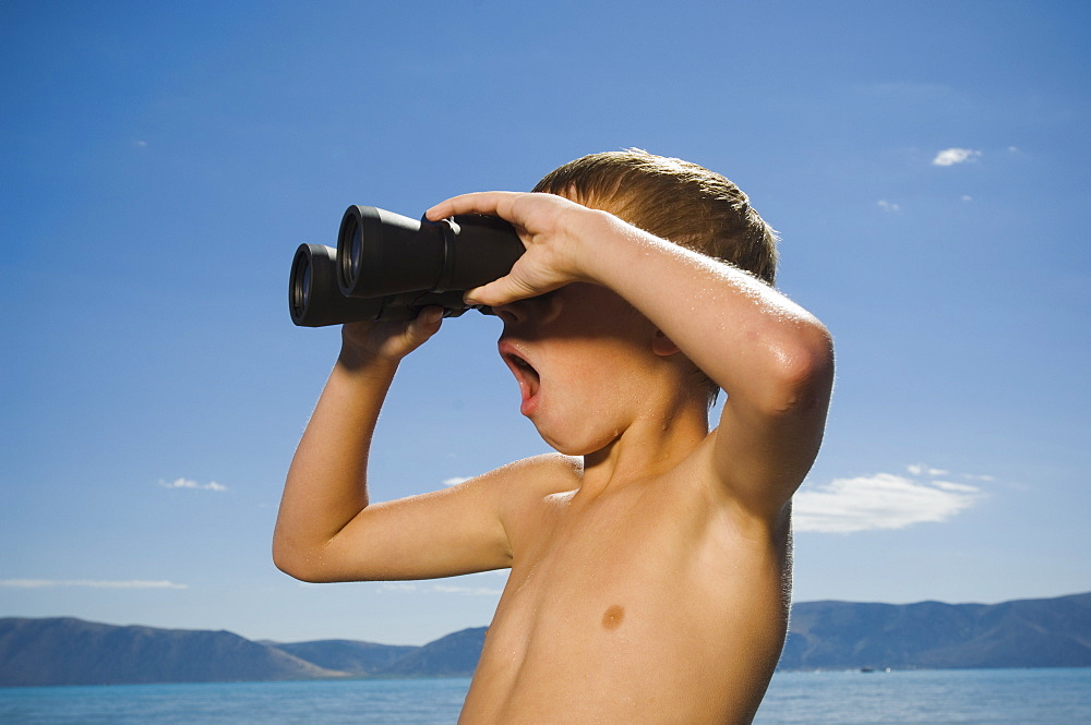 Boy looking through binoculars, Utah, United States
