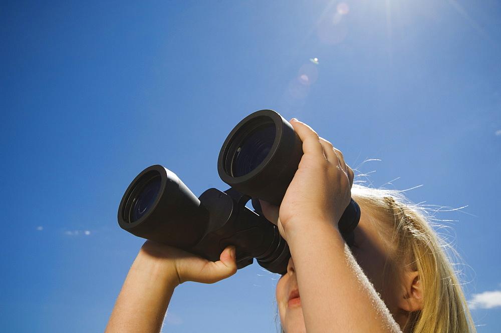 Girl looking through binoculars, Utah, United States