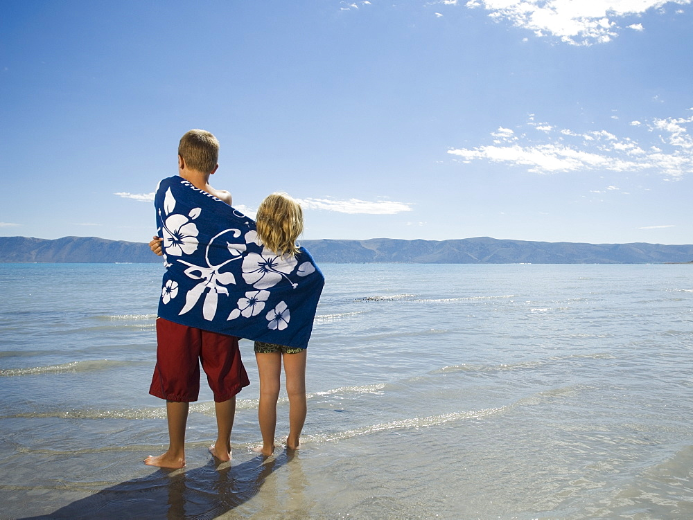 Brother and sister wrapped in beach towel, Utah, United States