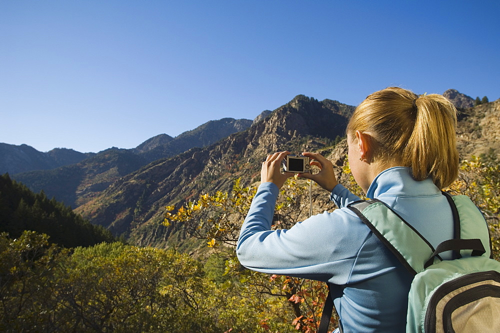Woman taking photograph of valley, Utah, United States