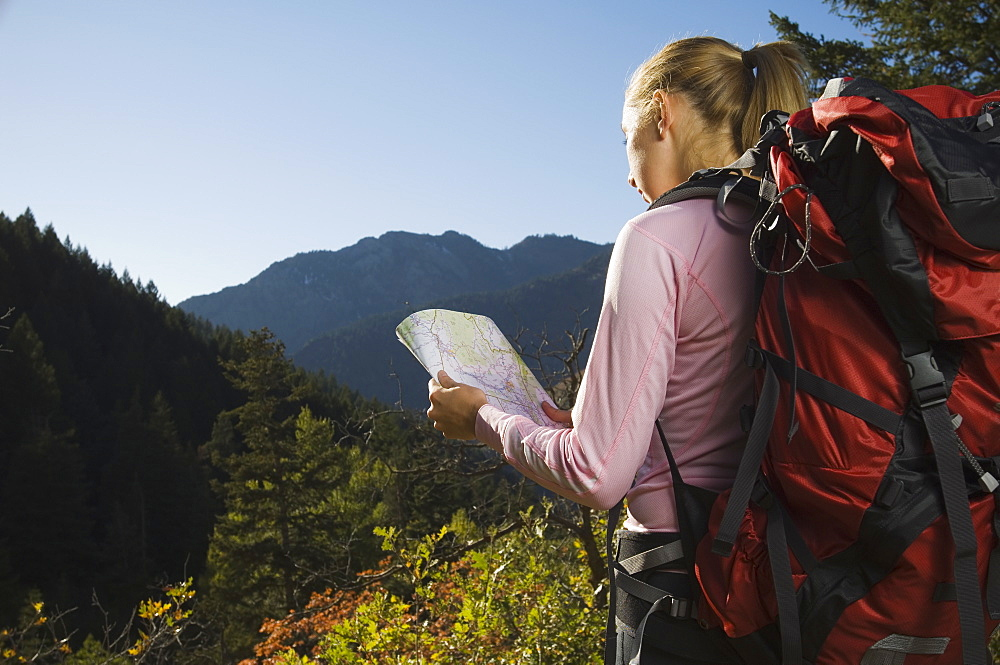 Female hiker looking at map, Utah, United States