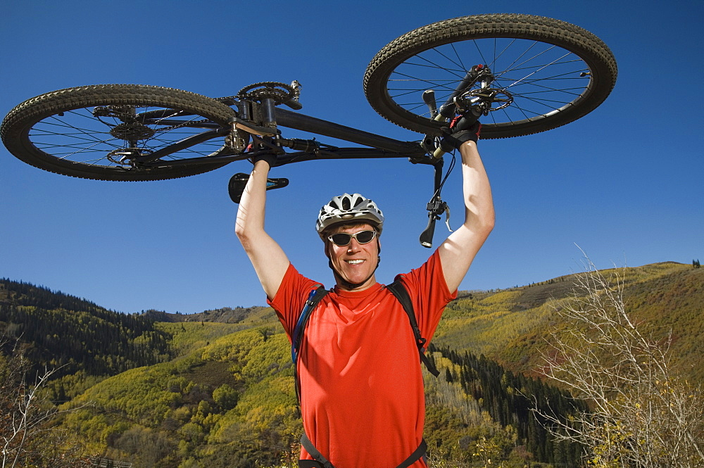 Man holding mountain bike over head, Utah, United States