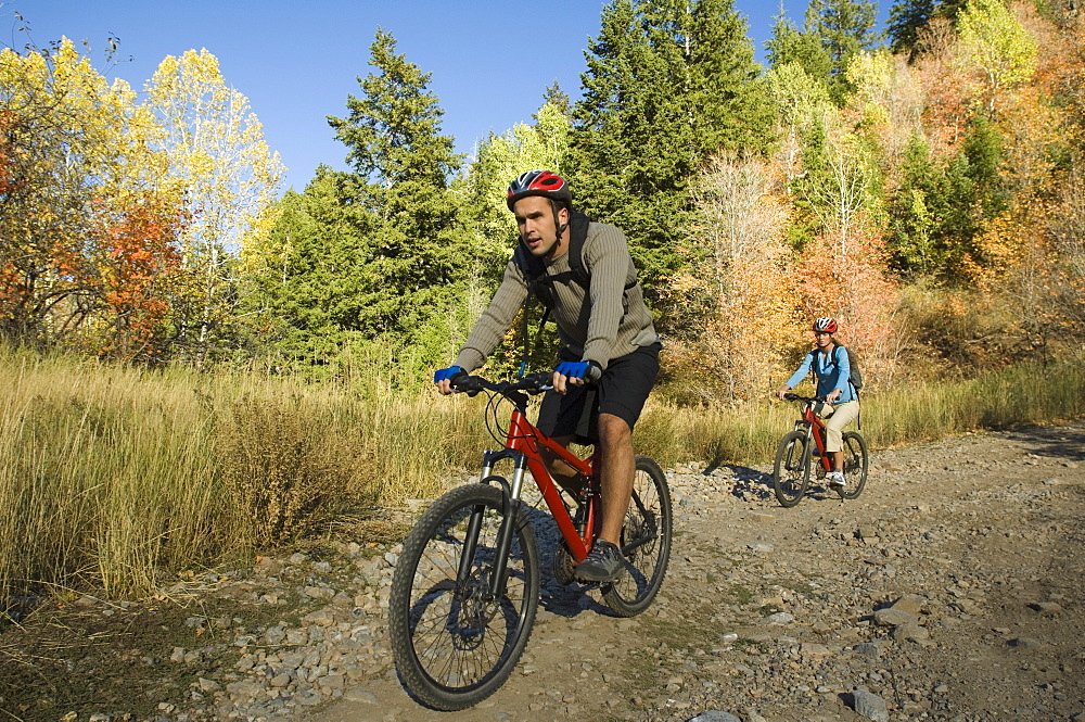 Couple riding mountain bikes, Utah, United States