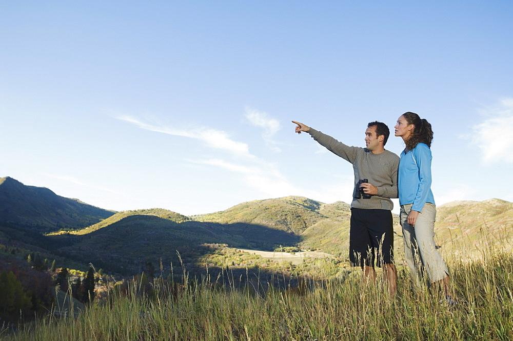Couple holding binoculars and pointing, Utah, United States