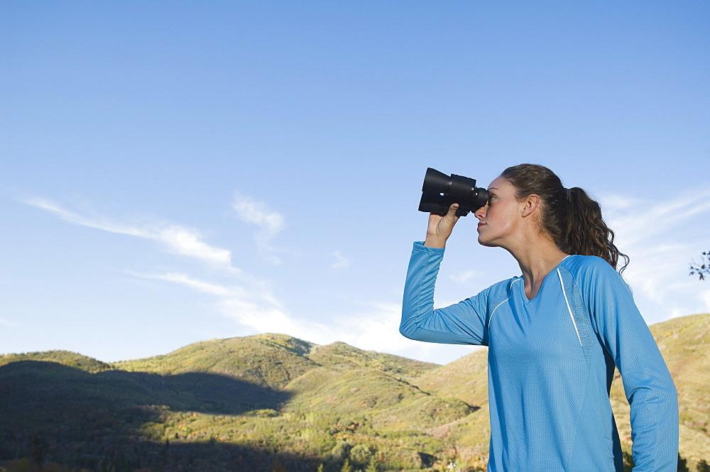Woman looking through binoculars, Utah, United States