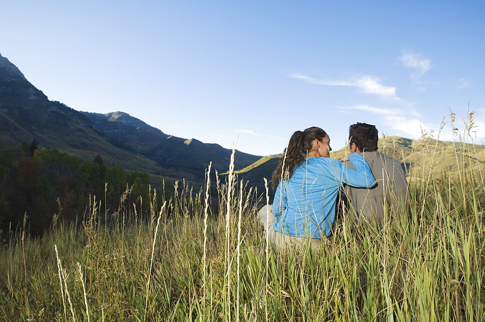 Couple sitting on hillside, Utah, United States