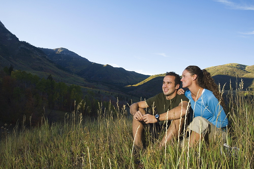 Couple sitting on hillside, Utah, United States