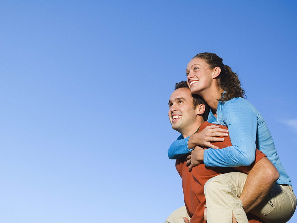Man giving girlfriend piggy back ride, Utah, United States
