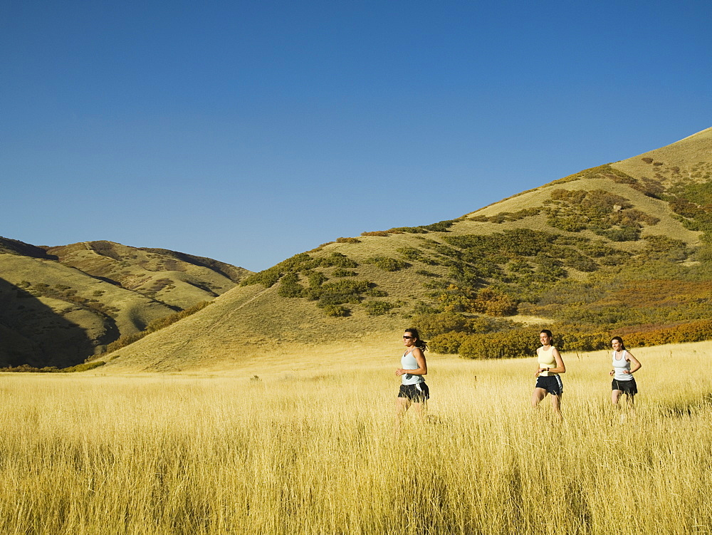 Group of people running in field, Utah, United States