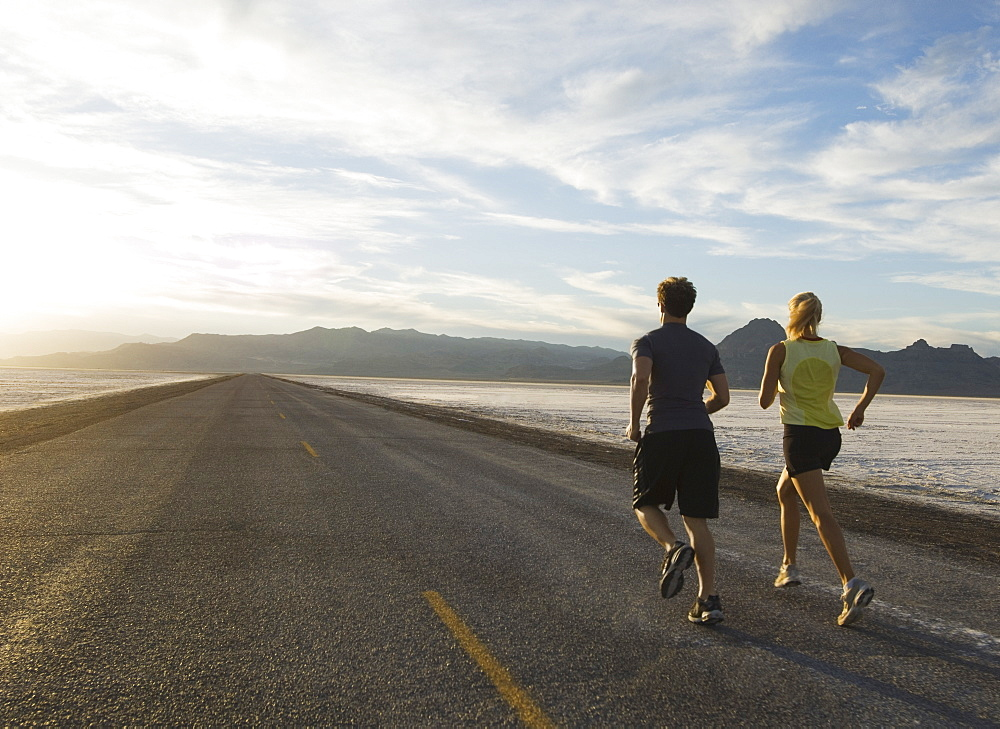 Couple running on road, Utah, United States