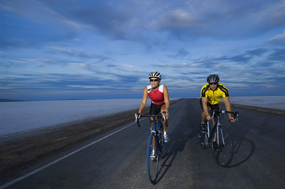 Couple cycling on road, Utah, United States