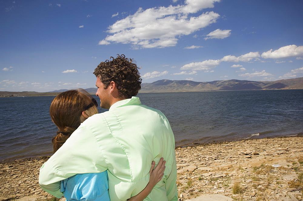 Couple hugging in front of lake, Utah, United States