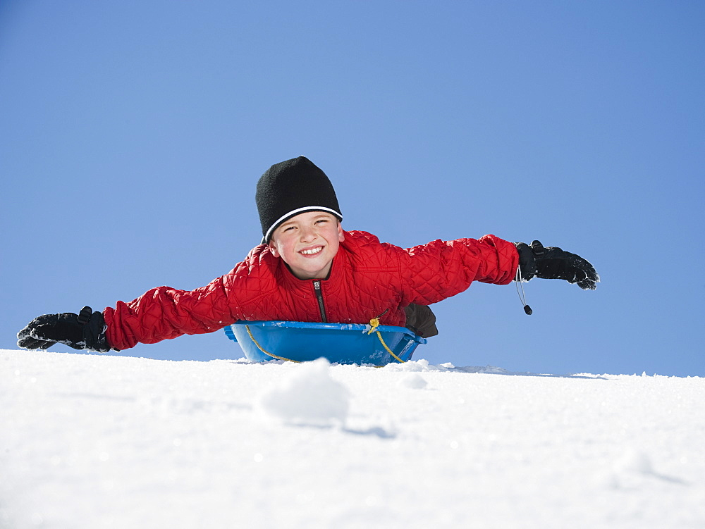 Boy laying on sled in snow