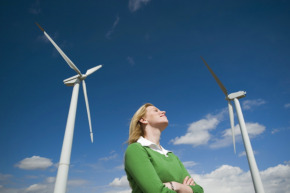 Low angle view of woman and wind turbines
