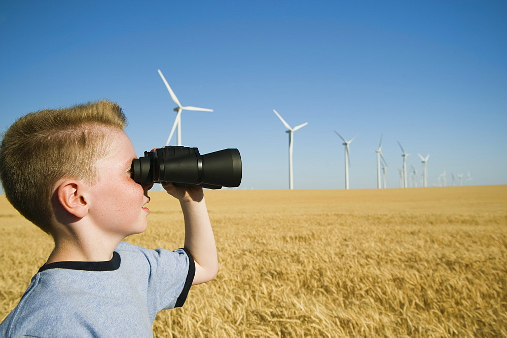 Boy on wind farm looking through binoculars