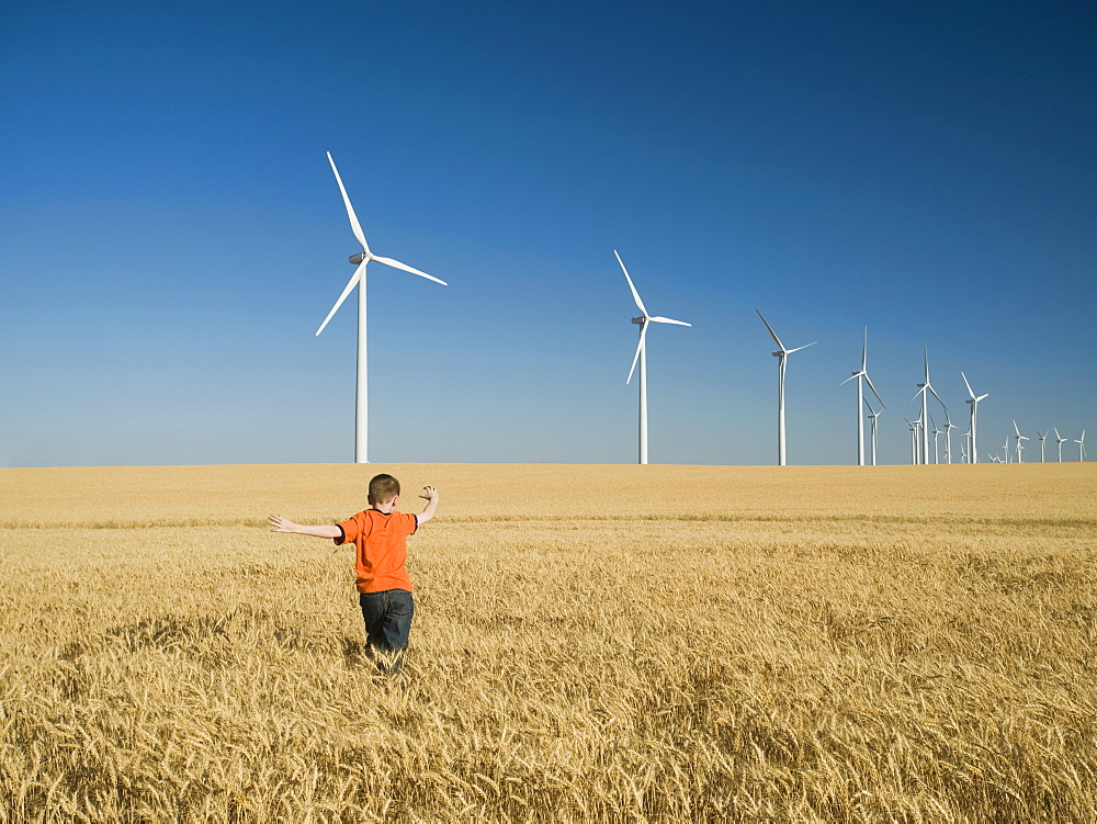 Boy running through field on wind farm - 1178-22163