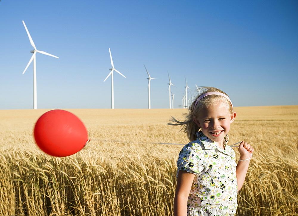 Girl holding balloon on wind farm