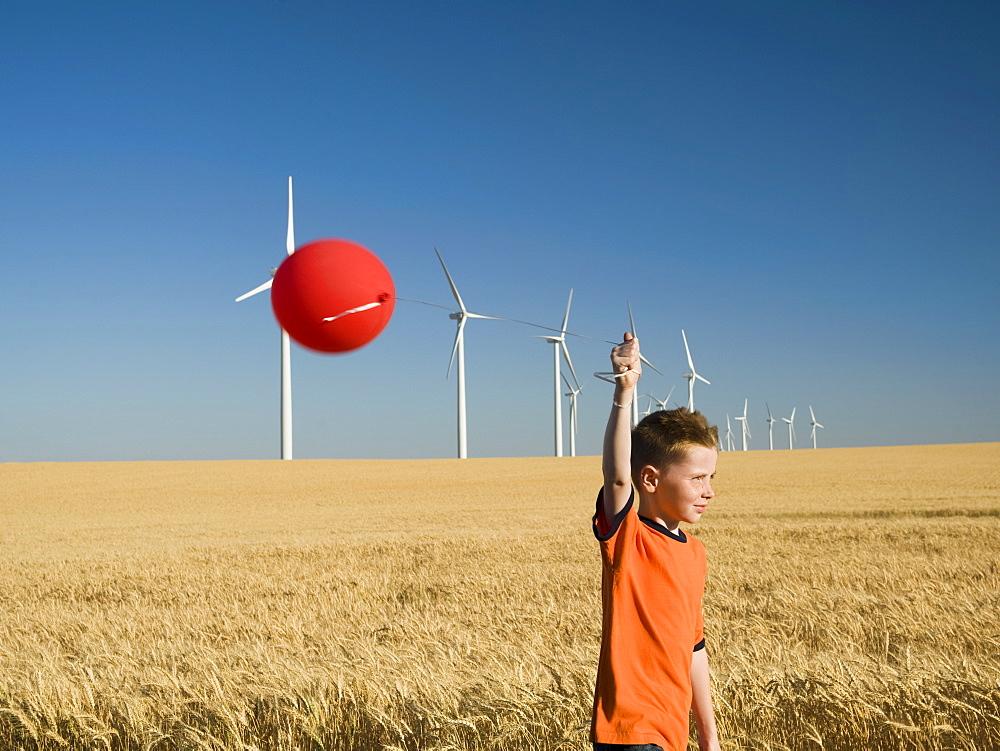 Boy holding balloon on wind farm