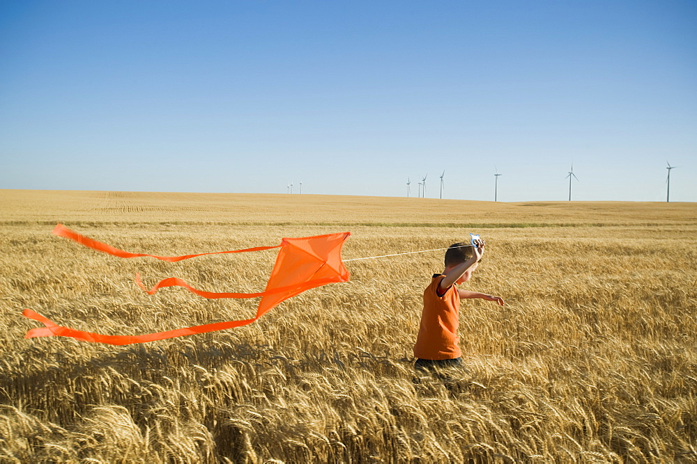 Boy running with kite on wind farm