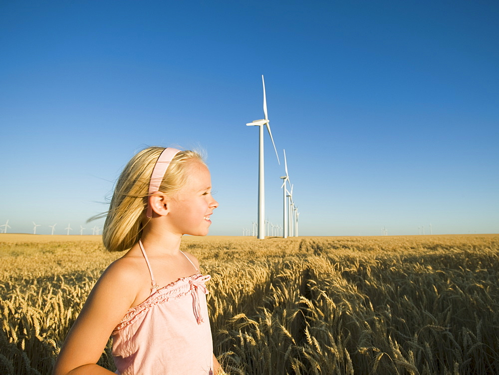 Girl in tall wheat field on wind farm