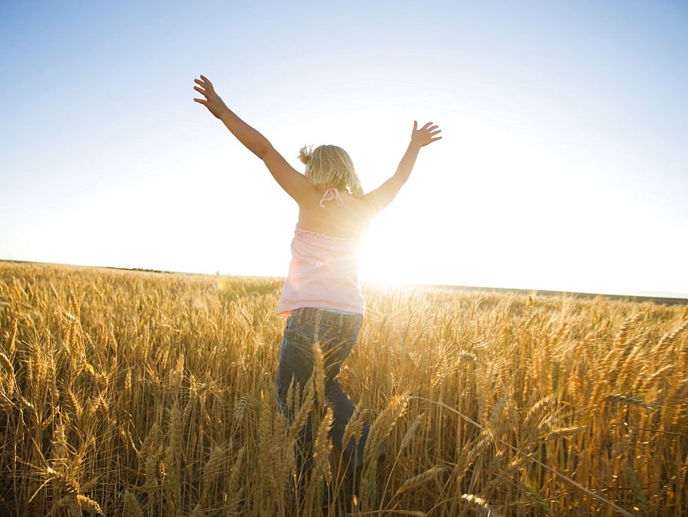 Girl jumping in tall wheat field