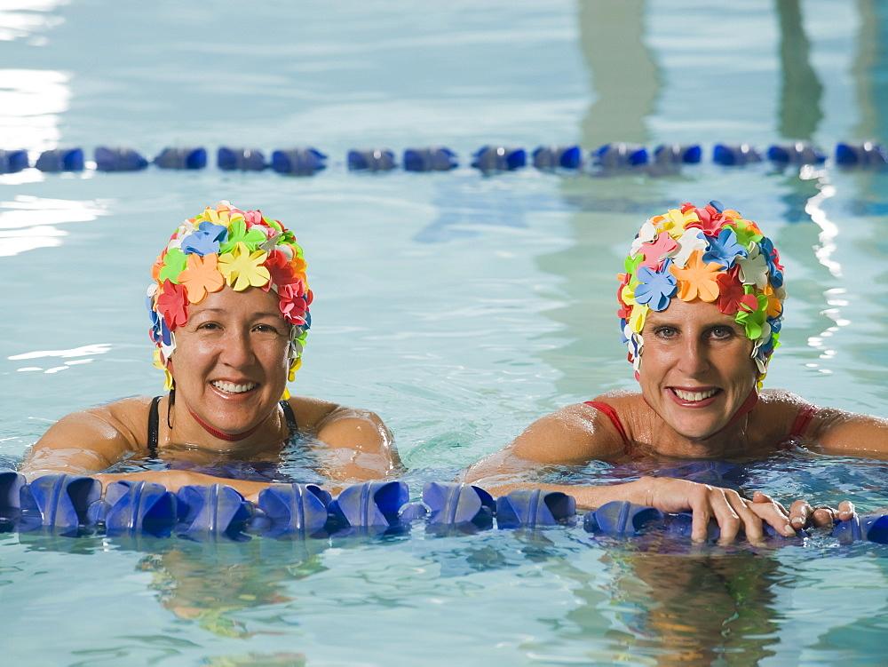 Women in swim caps posing in swimming pool