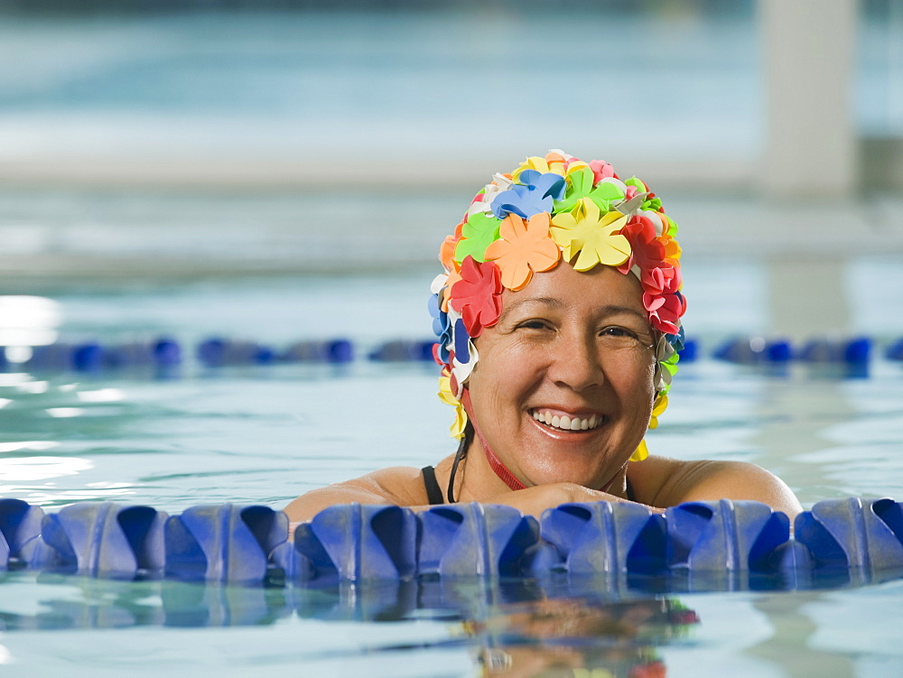 Woman in swim cap posing in swimming pool