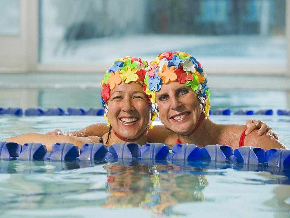 Women in swim caps hugging in swimming pool