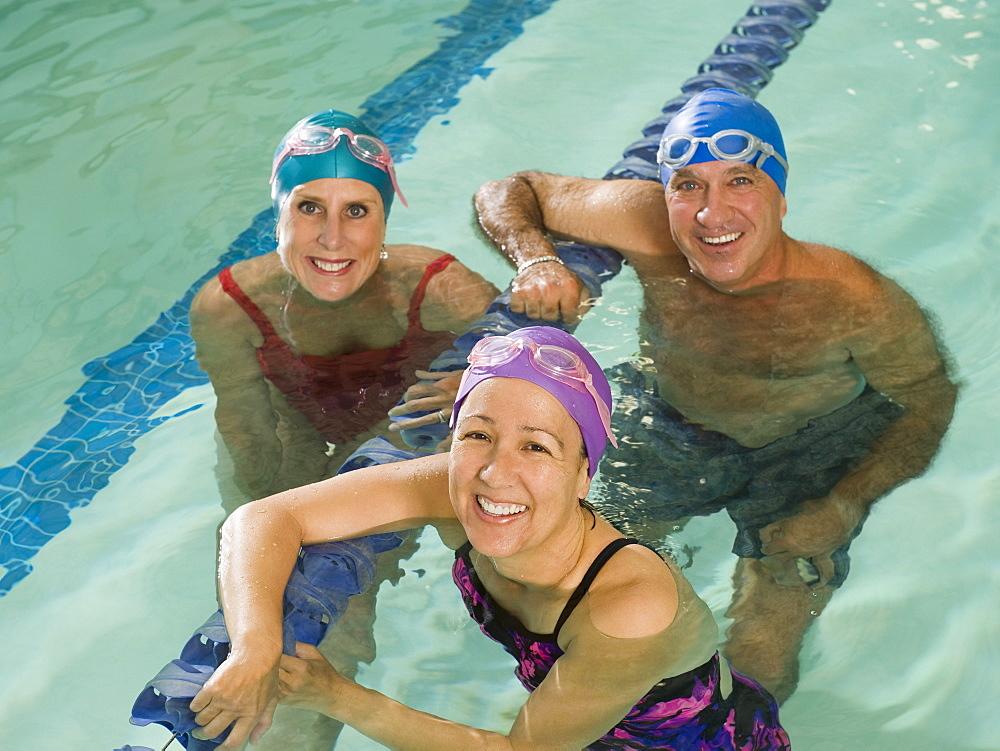 Man and women posing in swimming pool