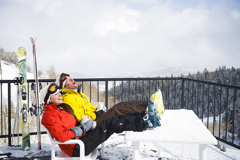 A couple relaxing on deck at ski resort