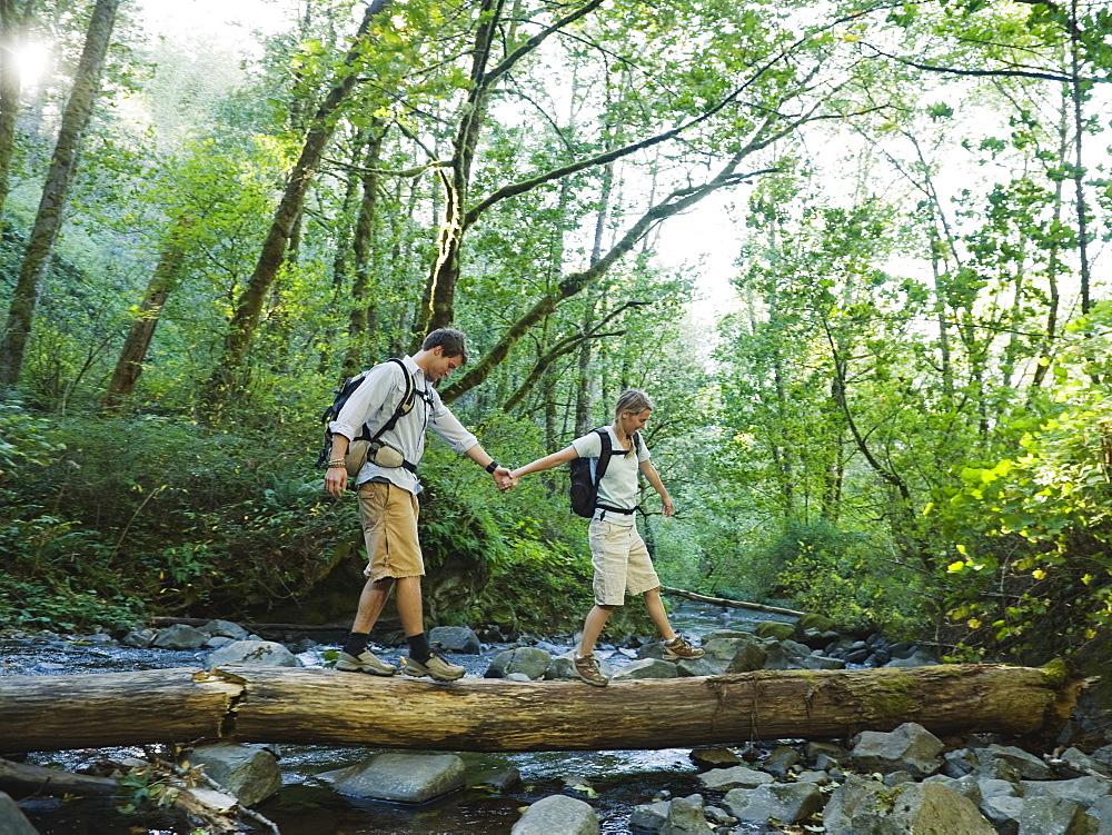Hikers walking on log