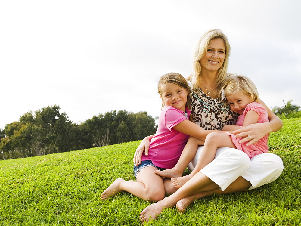 Mother and daughters sitting on grass