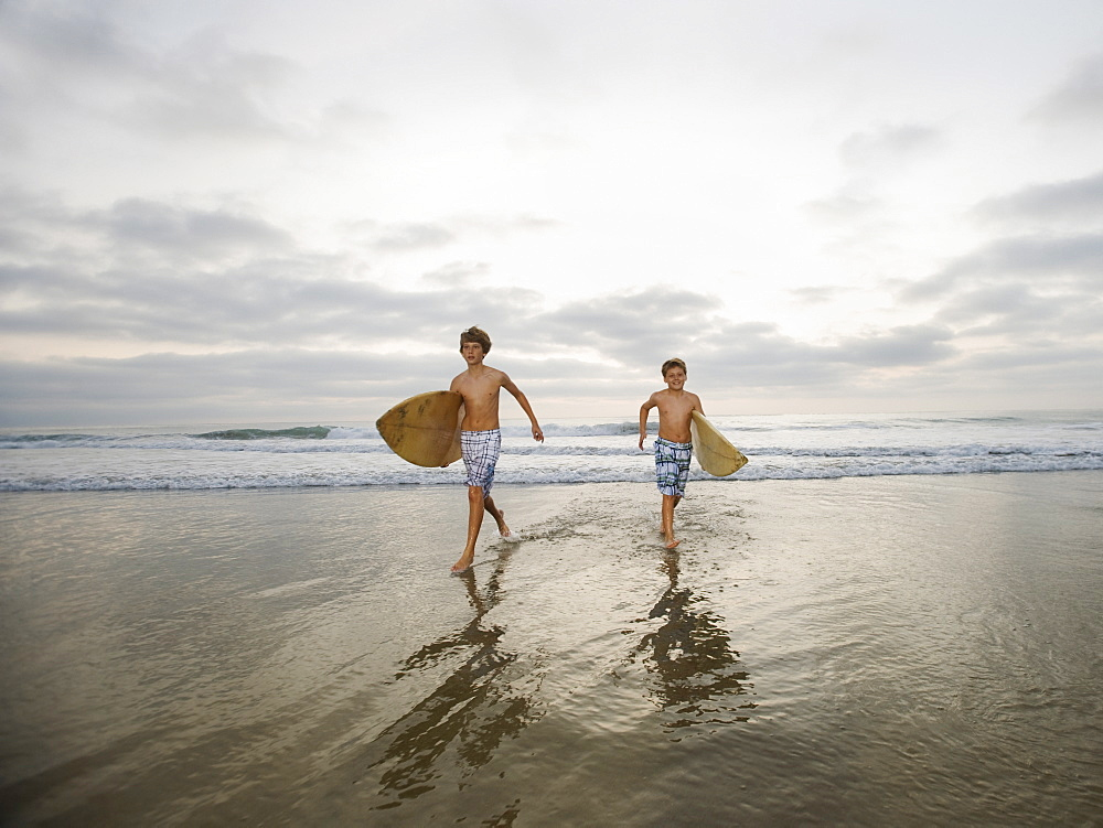 Boys running with surfboards