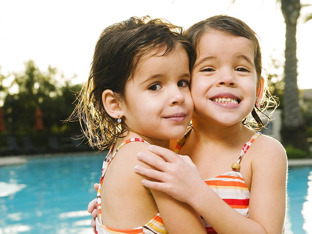 Sister embracing beside pool