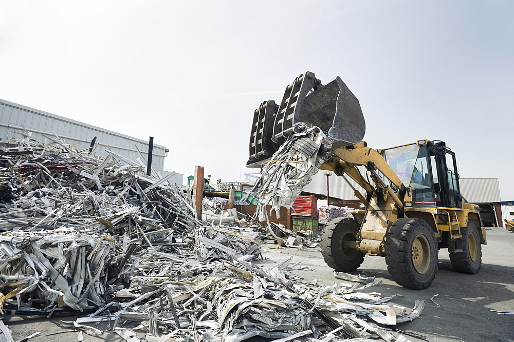 Backhoe dumping recyclable metal