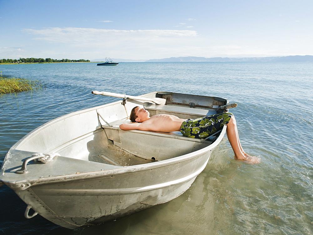 Boy (10-11) resting on boat
