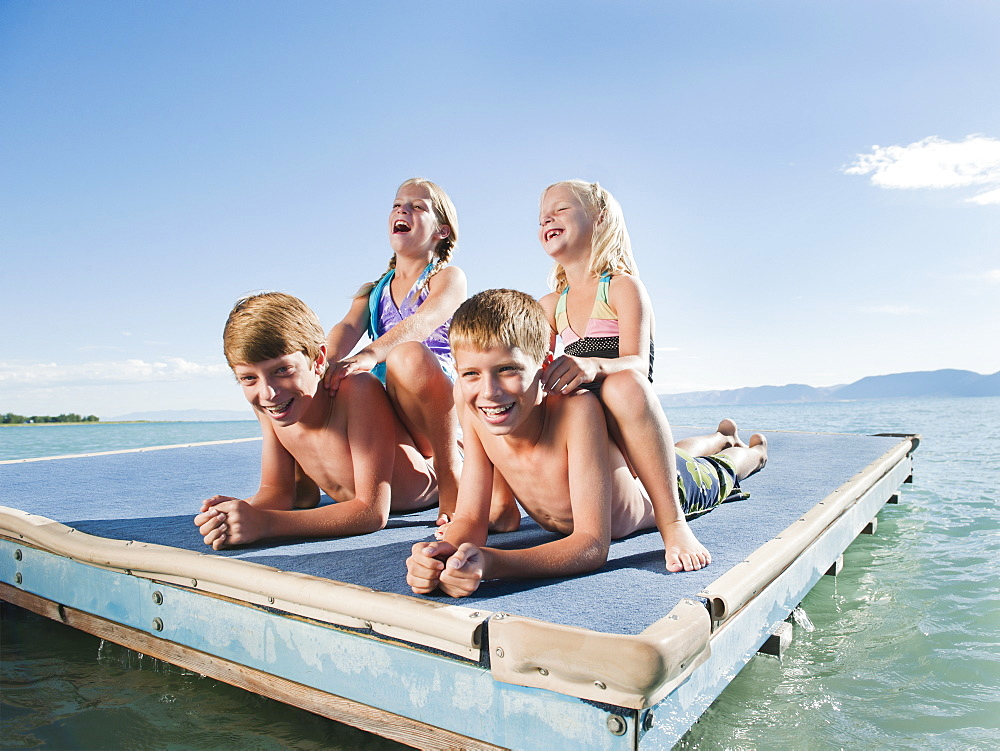 Kids (6-7,8-9,10-11,12-13) playing on raft on lake