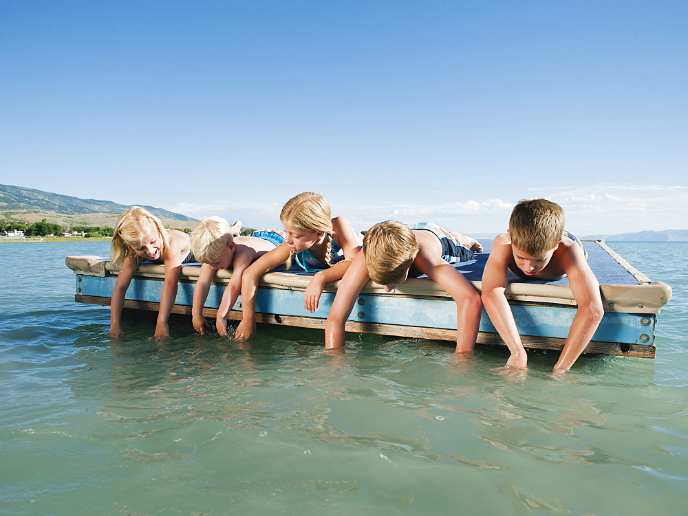 Kids (2-3,6-7,8-9,10-11,12-13) playing on raft on lake