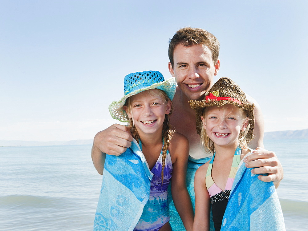 Portrait of girls (6-7,8-9) wrapped in towel on beach with their father