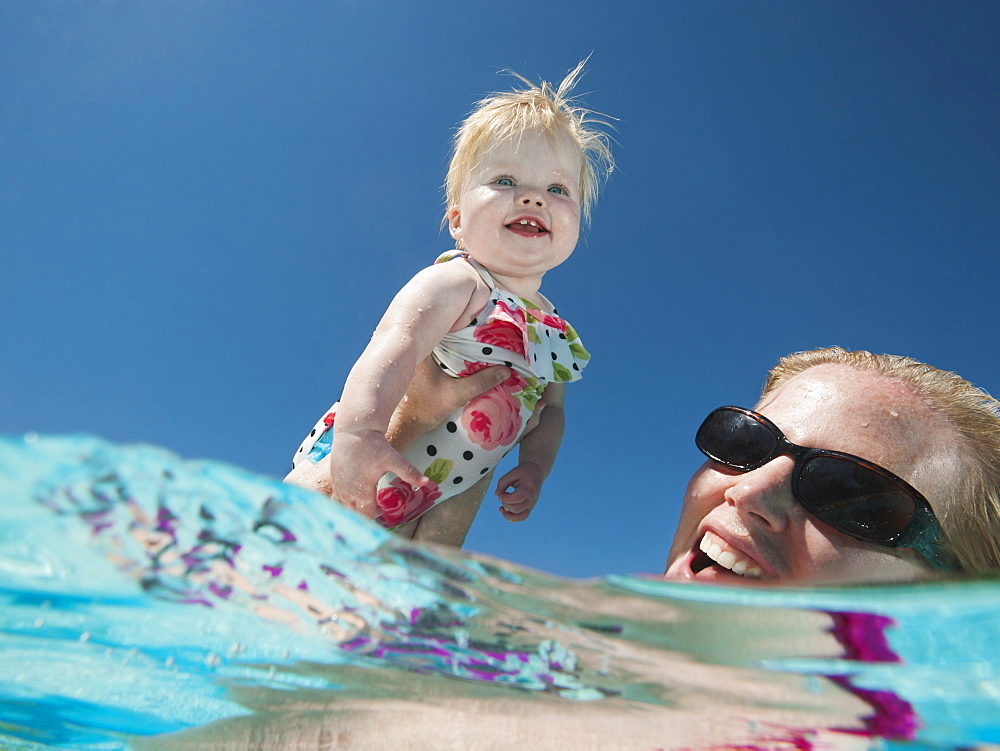 Mother and daughter (12-18months) playing at swimming pool