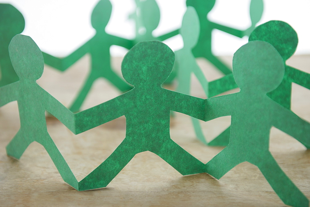Human silhouettes cut out from green paper