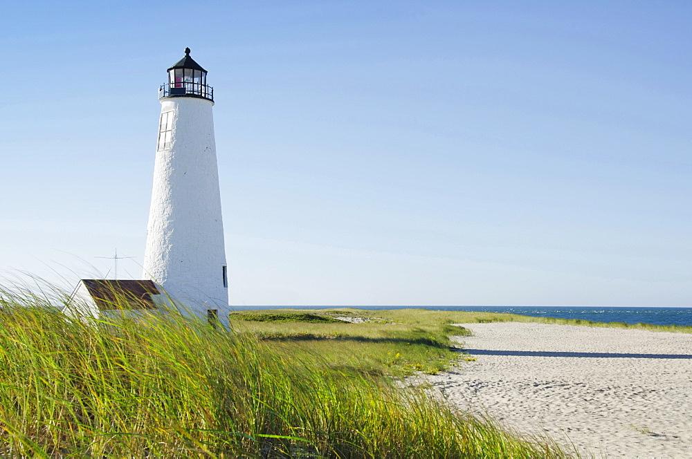 Great Point Lighthouse on overgrown beach against clear sky, Nantucket, Massachusetts, USA