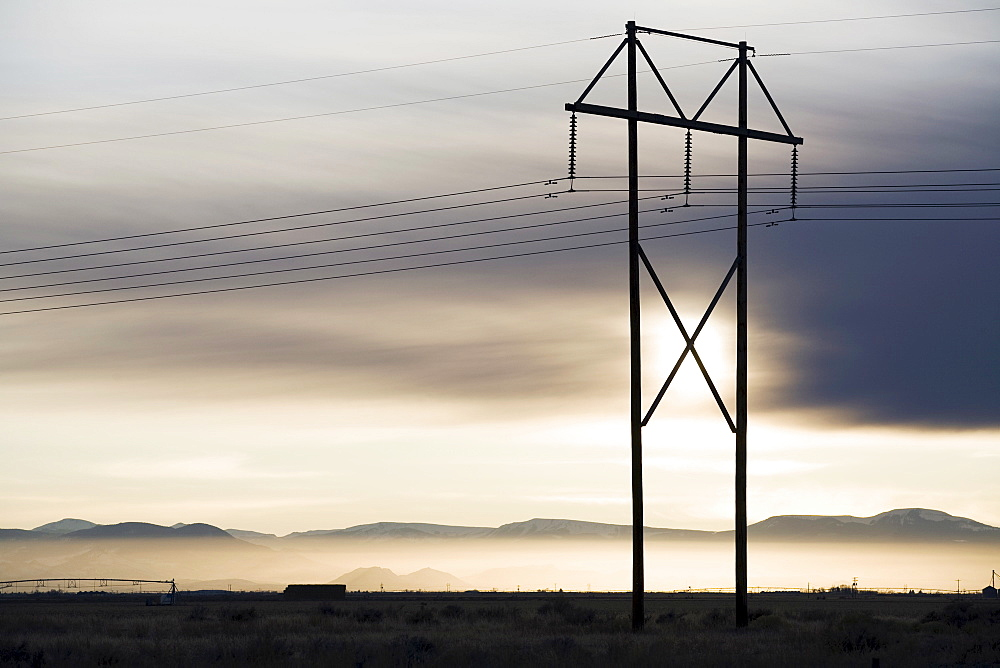 Power lines and tower at sunset, Colorado, USA